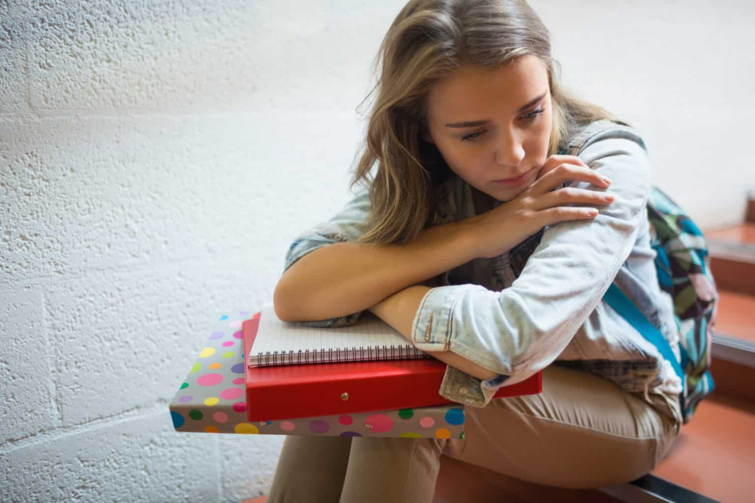 sad student sitting on stairs with textbooks in lap
